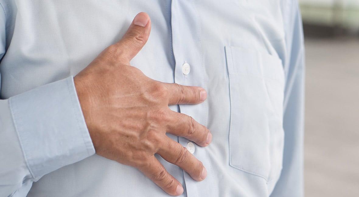 hand of senior old man holding chest