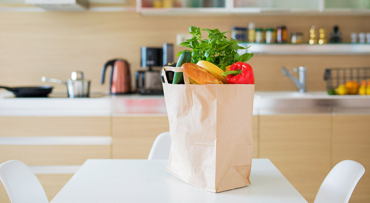 Paper shopping bag full with groceries products on kitchen table